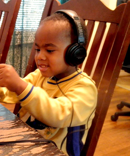 Little boy sitting at kitchen table wearing headphones