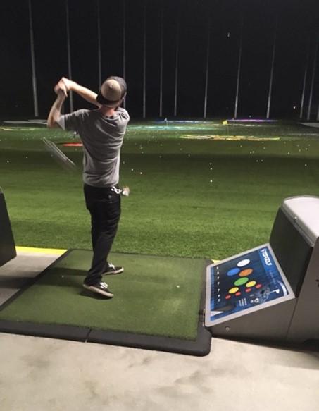man swinging a golf club at a top golf range