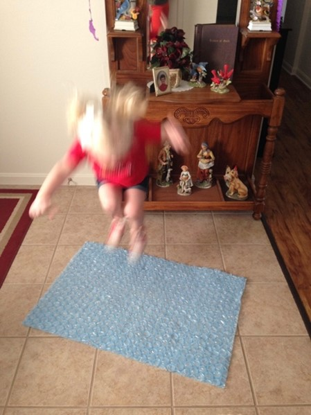 little girl jumping on bubble wrap to stimulate the eustachian tubes